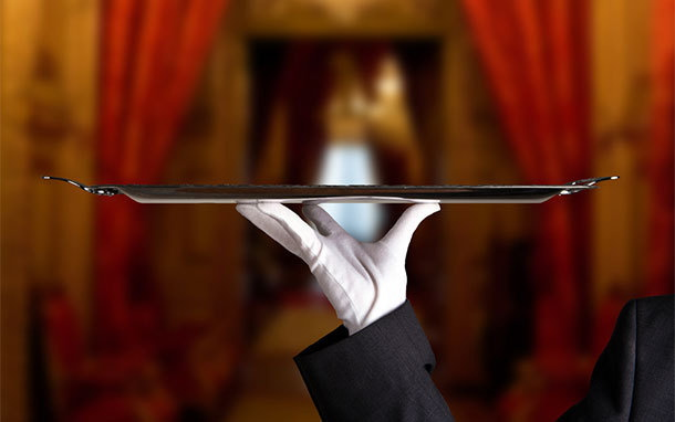 A waiter holding up a tray