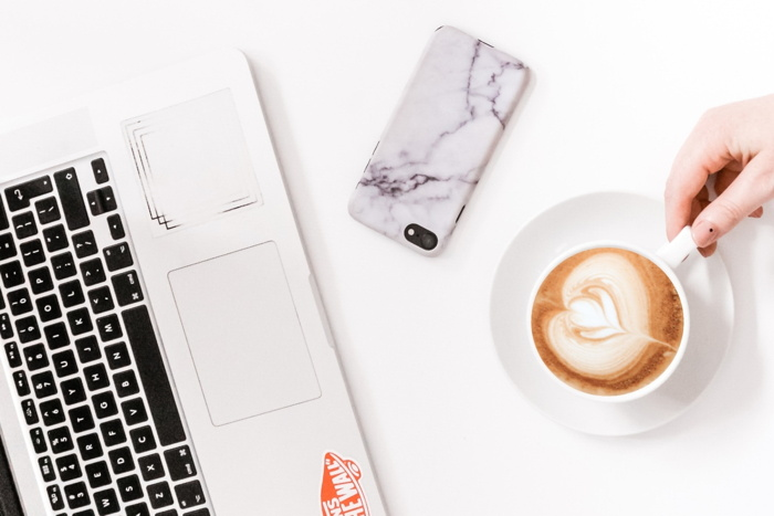 A laptop, phone and coffee on a desk