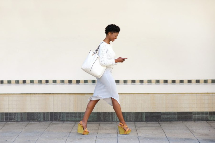 A woman walking and looking at a mobile phone
