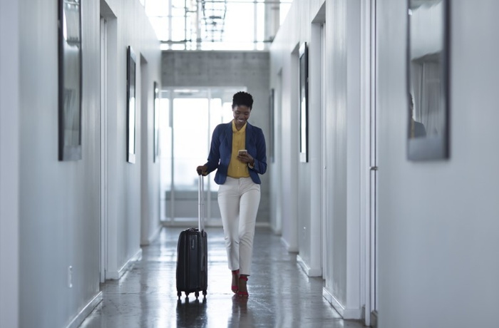 A woman pulling luggage in a corridor