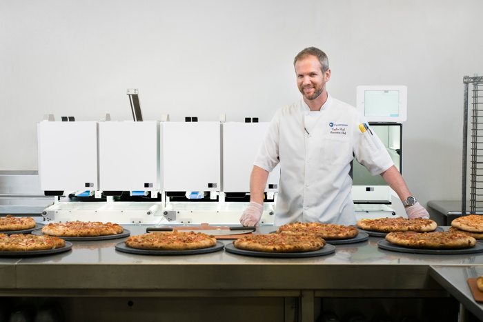 Centerplate Executive Chef Taylor Park stands in front of Picnic's automated pizza assembly robot at T-Mobile Park, home of the Seattle Mariners.