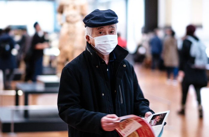 man in black coat holding book and wearing a mask - Unsplash