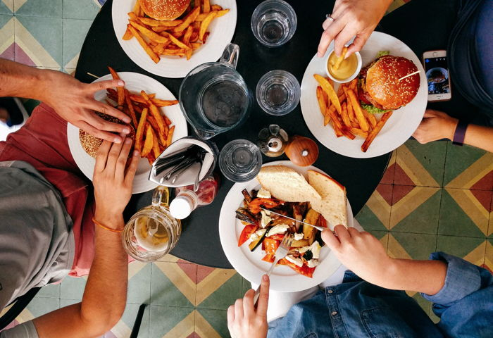 Four persons eating at a black wooden table - Unsplash