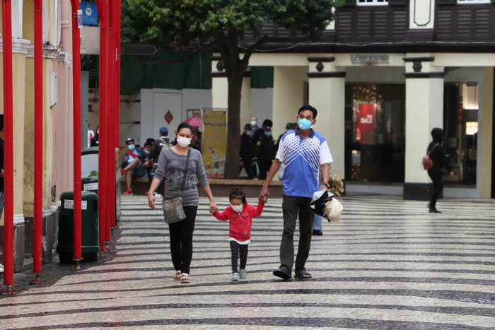 Family walking at Macau's Senado Square wearing protective face masks - Unsplash
