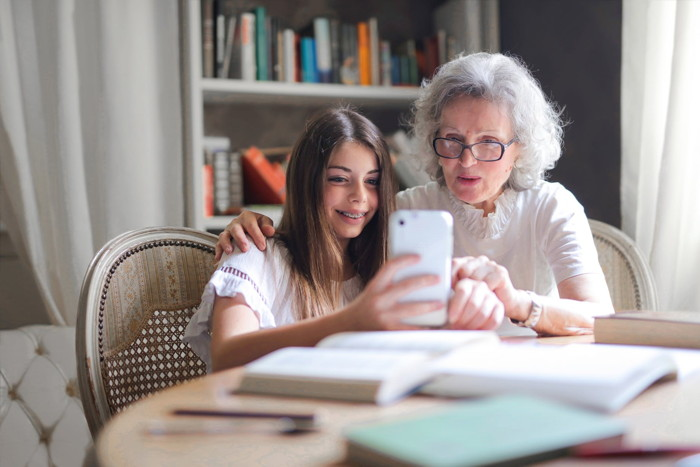 An older woman and a child looking at a smartphone