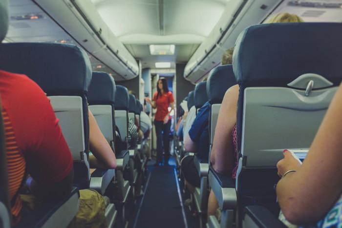 flight attendant standing between passenger seats - Unsplash