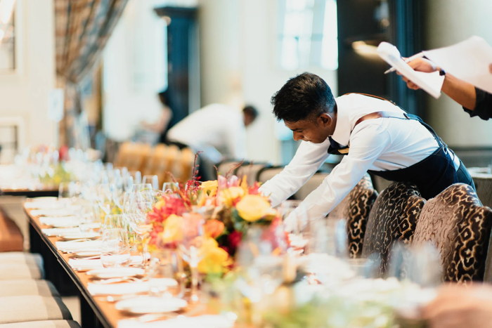 Waiter in white top standing next to a table - Unsplash