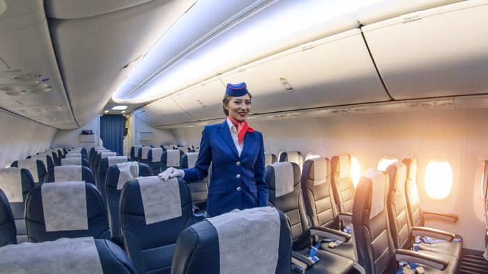 A flight attendant in an empty airplane