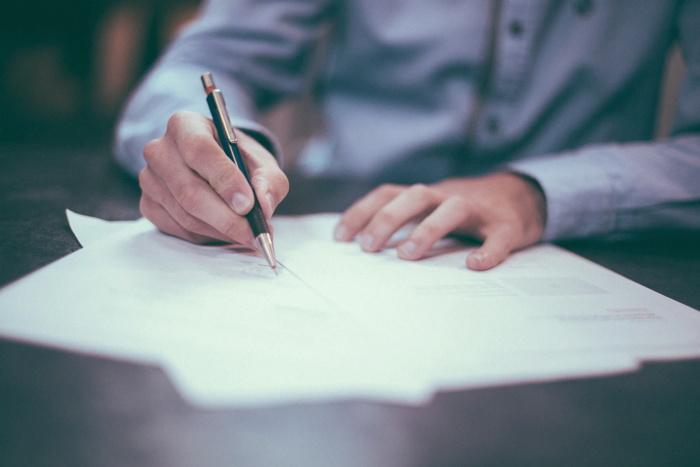 A man signing a document - Unsplash
