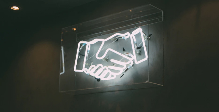 A neon sign of two hands shaking - Unsplash