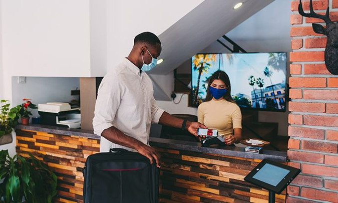 A person checking into a hotel wearing a face mask - Source HFTP