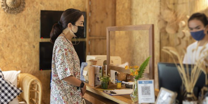 A person checking into a hotel wearing a face mask - Source STAAH
