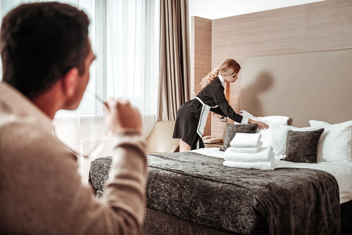 A man looking at a room attendant in a hotel room