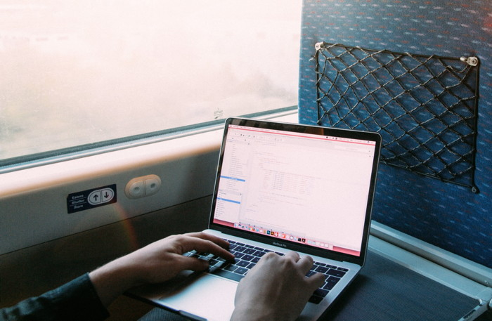 A person using a laptop on a train