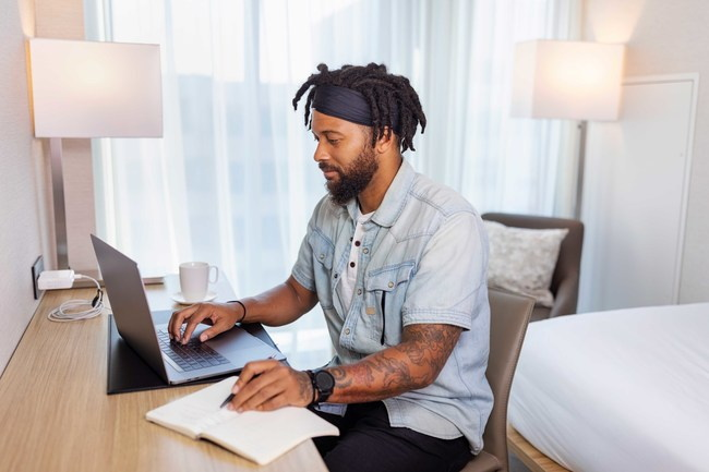 A man working at a desk in a hotel room