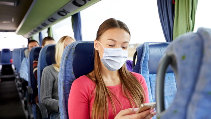 A women on a bus wearing a face mask - Source UNWTO