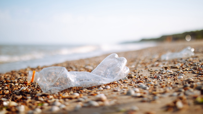 An empty plastic bottle on a beach  - Source UNWTO