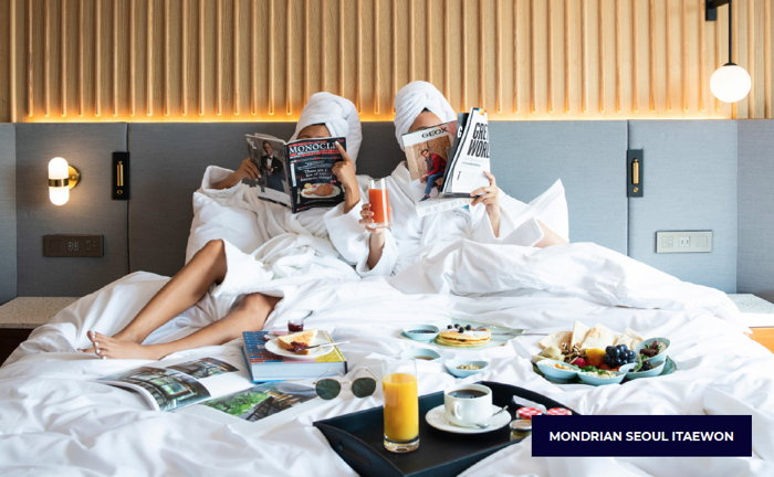 Two people in bed reading magazines