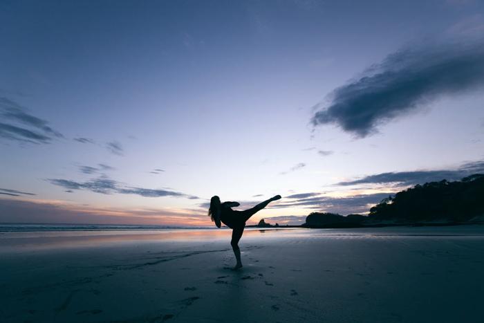 A kick boxer on a beach - Unsplash