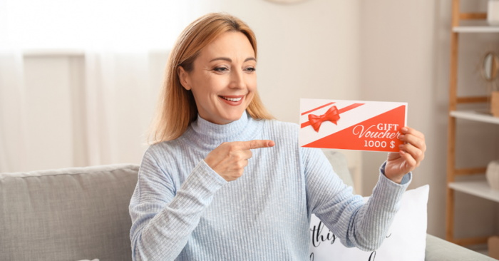 A woman holding a gift voucher - Source STAAH