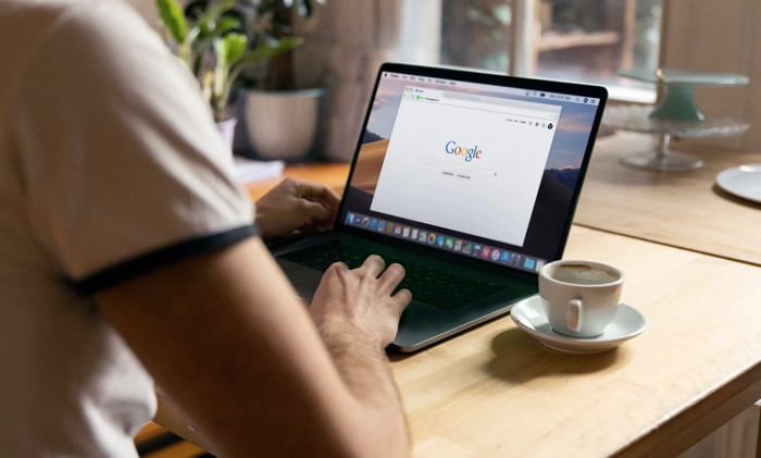 Man uses Apple MacBook in a cafe or restaurant. He is searching Google website. - Unsplash
