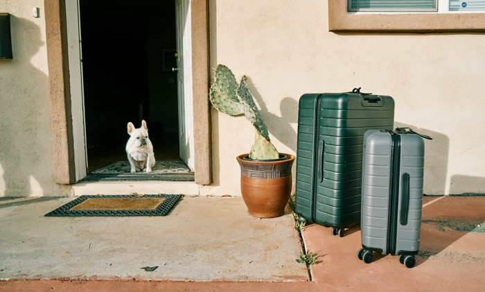 Suitcases in front of a house - Unsplash