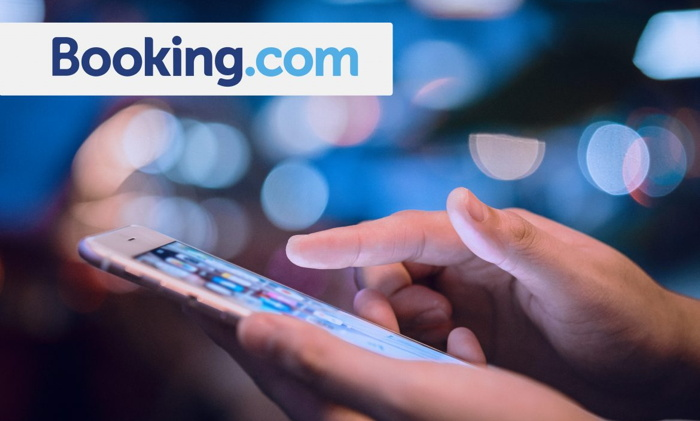 Booking.com logo and a mobile phone - Source STAAH