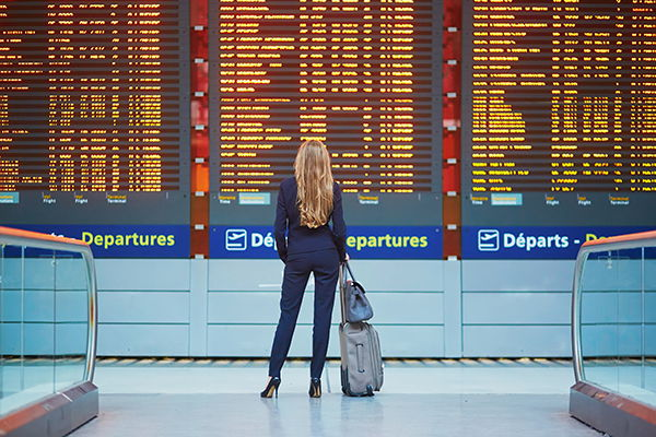 A person in front of an airport departure board - Source WTTC