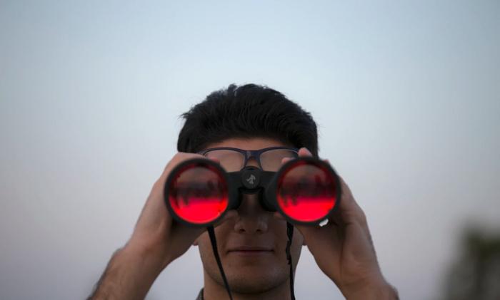 A man holding binoculars - Unsplash @mostafa_meraji