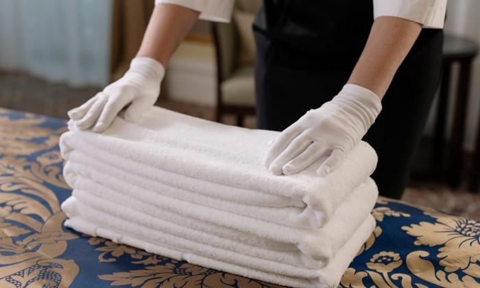 Una persona que dobla toallas - fuente TrustYou