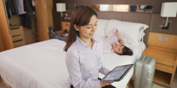A person using a tablet on a hotel bed