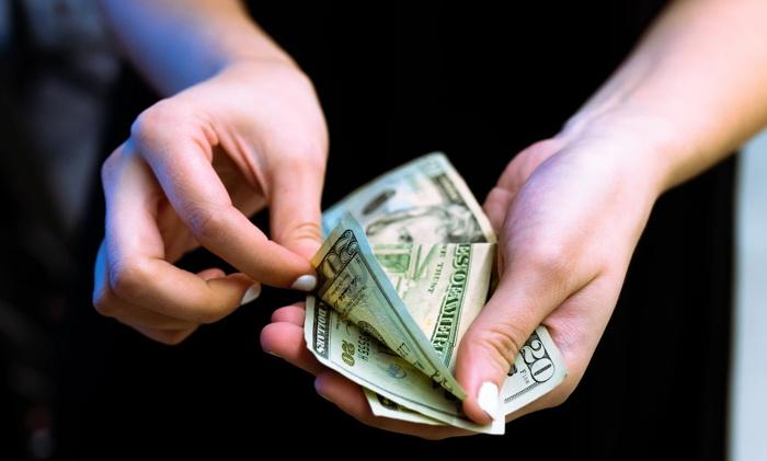 A person counting dollar bills - Unsplash